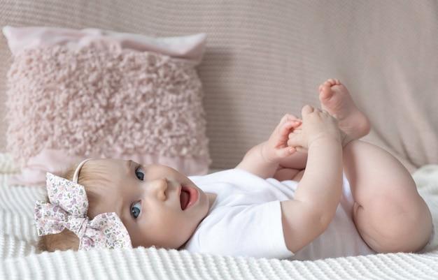 Nettes kleines lustiges kaukasisches blondes baby mit rosa schleife auf kopf liegend ob bett auf oberfläche der dekorativen kissen zu hause