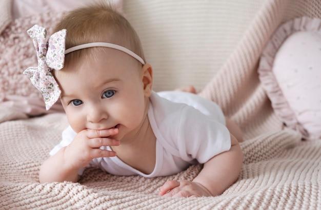 Nettes kleines lustiges nachdenkliches kaukasisches blondes baby mit rosa schleife auf kopf liegend ob bett, das finger in mund setzt