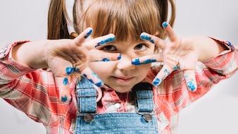 Nettes kleines Mädchen, das mit den gemalten Fingern steht