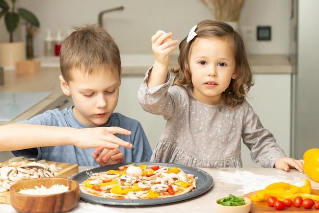 Nettes kleines mädchen 2-4 im grauen kleid und junge 7-10 im t-shirt, das pizza zusammen in der küche kocht. bruder und schwester kochen
