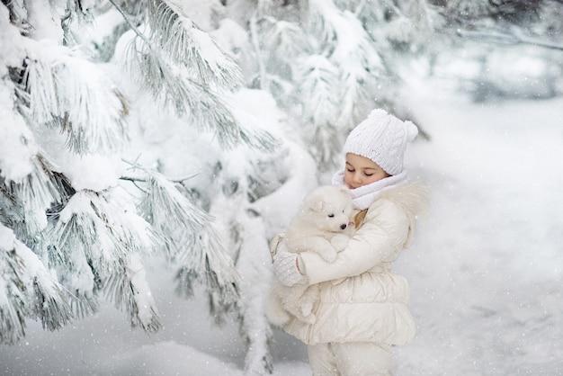 Nettes kleines mädchen 4 jahre alt mit einem flauschigen weißen welpen im winterwald