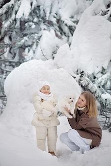 Nettes kleines mädchen 4 jahre alt und ihre schöne mutter mit einem flauschigen weißen welpen im winterwald