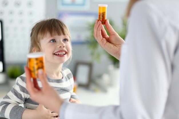 Nettes kleines mädchen an der doktoraufnahme, die medikationsverordnung erhält