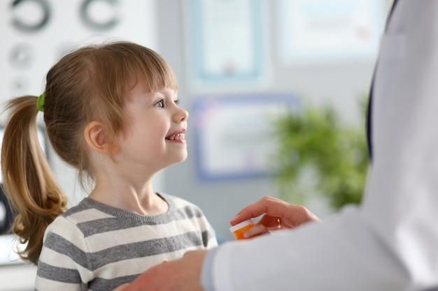 Nettes kleines mädchen an der rezeption des arztes, das verschreibungspflichtige medikamente erhält