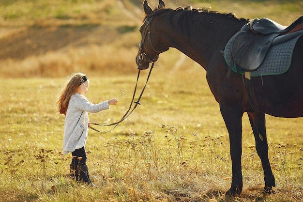Nettes kleines mädchen auf einem herbstgebiet mit pferd