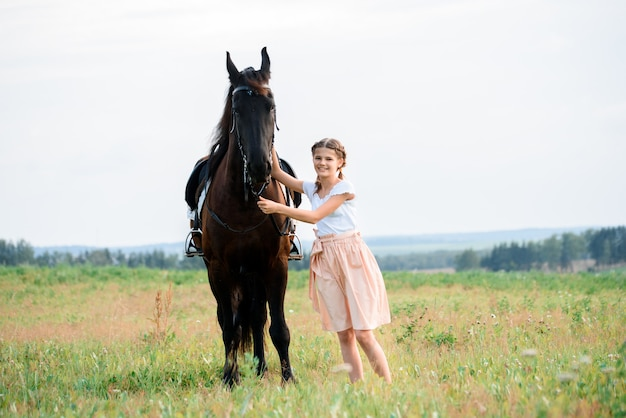 Nettes kleines mädchen auf einem pferd in einem sommerfeldkleid. sonniger tag