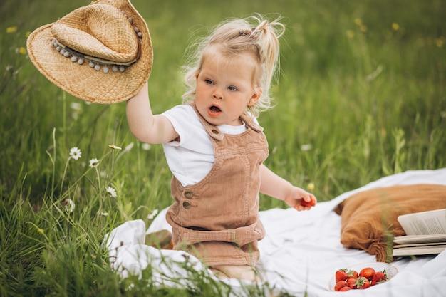 Nettes kleines mädchen auf picknick im park, der straberries isst