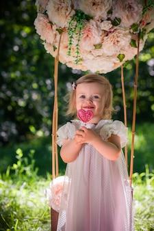 Nettes kleines mädchen bleibt mit süßigkeitsherz an der wand eines grünen grases und der bäume valentinstag