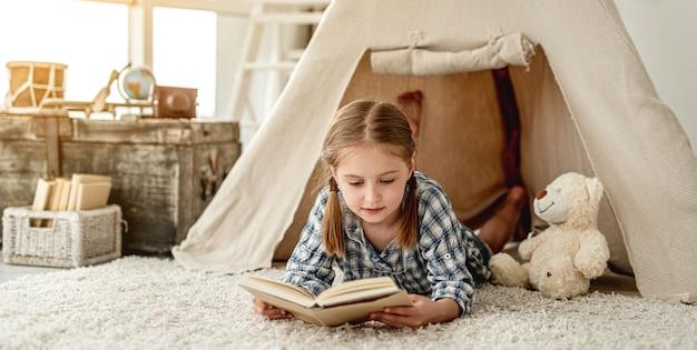 Nettes kleines mädchen, das abenteuerbuch liest