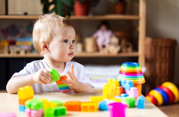 Nettes kleines mädchen, das allein mit vielen bunten plastikspielzeugen zu hause spielt.