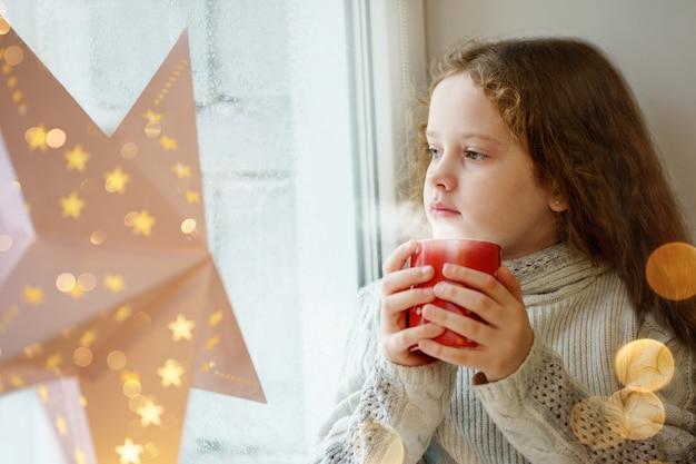 Nettes kleines mädchen, das am fenster mit einer schale heißem kakao sitzt und auf erstem fallendem schnee schaut