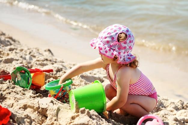 Nettes kleines mädchen, das am strand spielt