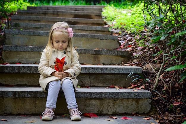 Nettes kleines mädchen, das auf den steinschritten in einem park sitzt und ein rotes blatt gefallen von einem baum hält