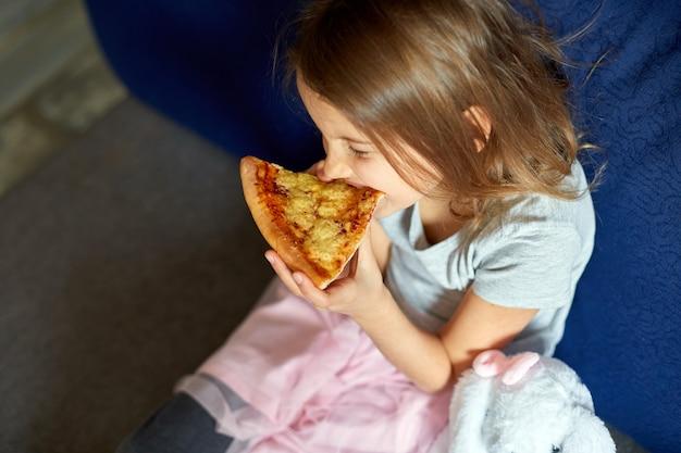 Nettes kleines mädchen, das auf der couch sitzt und zu hause ein stück italienische pizza isst, leckeres essen