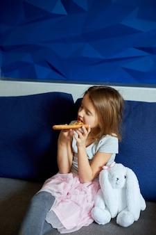 Nettes kleines mädchen, das auf der couch sitzt und zu hause ein stück italienische pizza isst