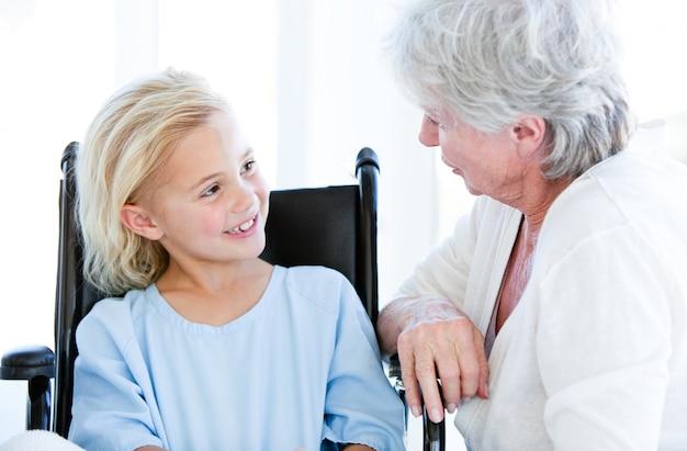 Nettes kleines mädchen, das auf einem rollstuhl spricht mit ihrer großmutter sitzt