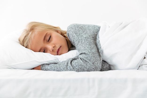 Nettes kleines mädchen, das auf weißem kissen im grauen pyjama mit angenehmen träumen schläft