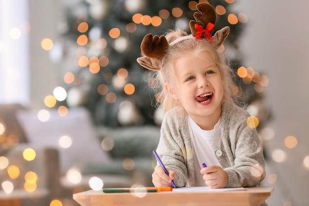 Nettes kleines mädchen, das brief an den weihnachtsmann zu hause schreibt