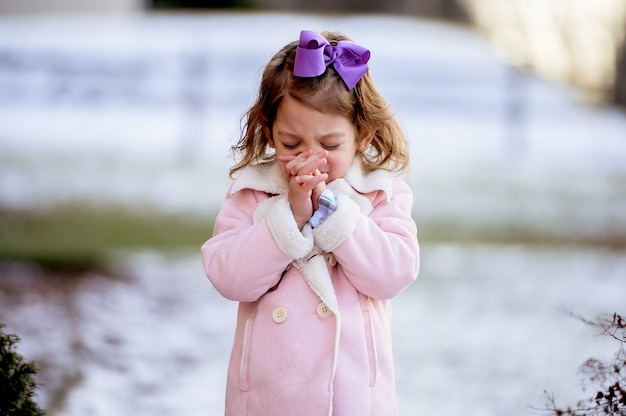 Nettes kleines mädchen, das ein lila band trägt, das in einem park betet
