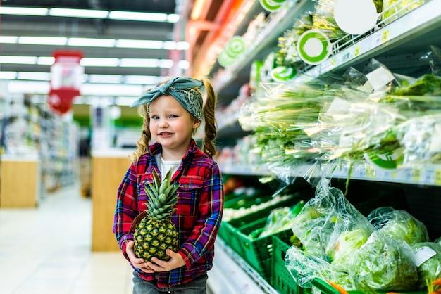 Nettes kleines mädchen, das eine ananas in einem lebensmittelgeschäft oder supermarkt hält
