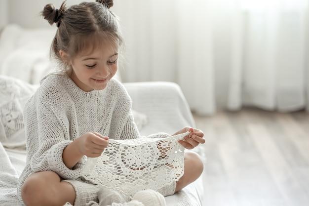 Nettes kleines mädchen, das eine handgemachte durchbrochene serviette in ihren händen hält.