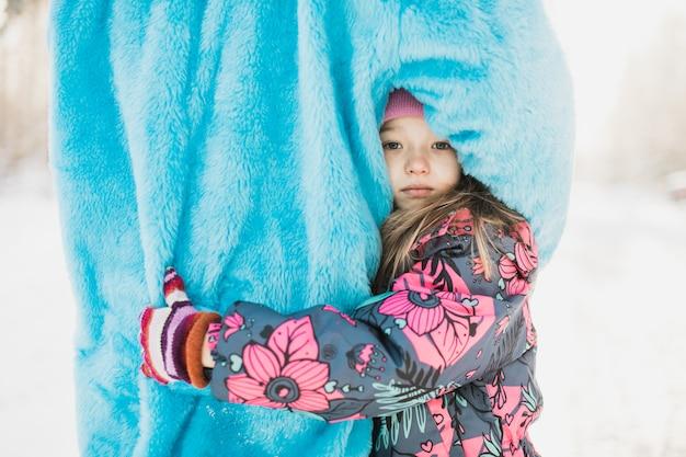 Nettes kleines mädchen, das eine person in einem flauschigen blauen kostüm umarmt