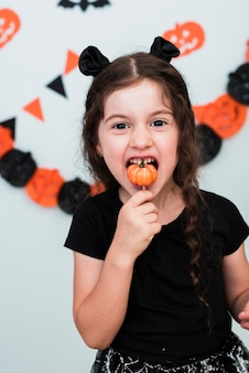 Nettes kleines mädchen, das eine pumpking süßigkeit isst