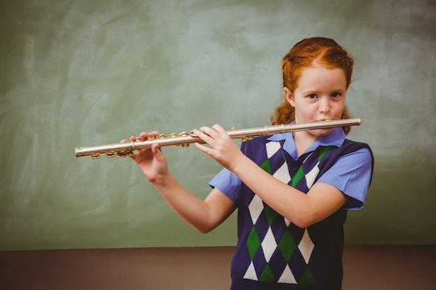 Nettes kleines mädchen, das flöte im klassenzimmer spielt