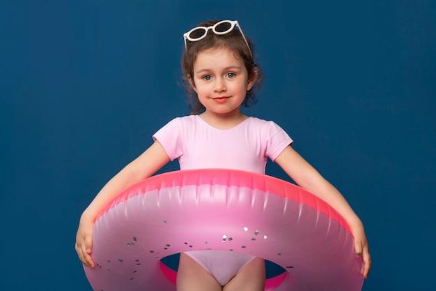 Nettes kleines mädchen, das für sommer mit einem schwimmring bereit ist
