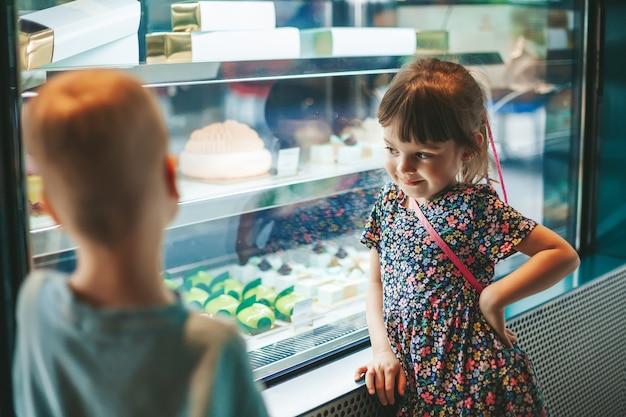 Nettes kleines mädchen, das gebäck in einem café auswählt zwei kinder, die kuchen auf einer anzeige in einer bäckerei betrachten