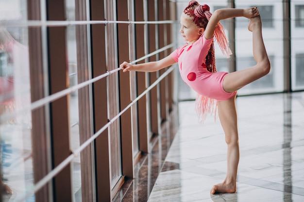 Nettes kleines mädchen, das gymnastik tut