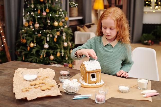 Nettes kleines mädchen, das hand über dach des lebkuchenhauses hält, verziert mit schlagsahne, während mutter mit festlichem nachtisch für weihnachten hilft