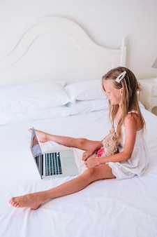 Nettes kleines mädchen, das hausarbeit auf laptop tut