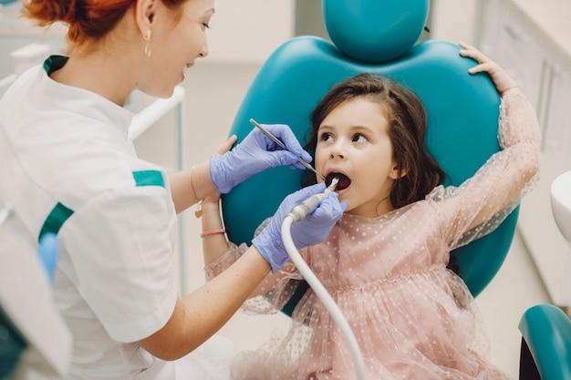 Nettes kleines mädchen, das ihren arzt beim durchführen einer zahnoperation in einer pädiatrischen stomatologie betrachtet.