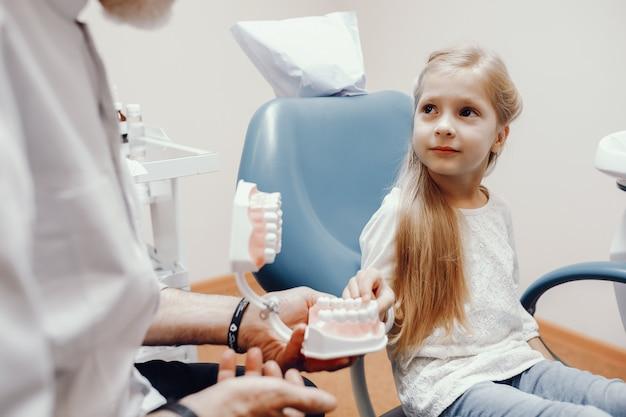 Nettes kleines mädchen, das im büro des zahnarztes sitzt