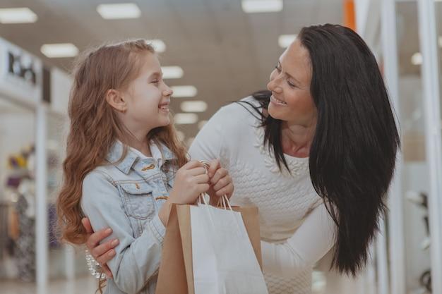 Nettes kleines mädchen, das im einkaufszentrum mit ihrer mutter kauft