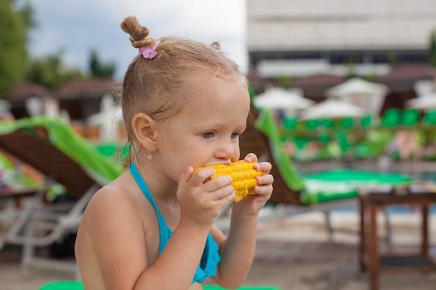 Nettes kleines mädchen, das im urlaub mais am pool isst