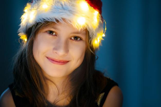 Nettes kleines mädchen, das in cristmas hut mit feenhaften weihnachtslichtern lächelt.
