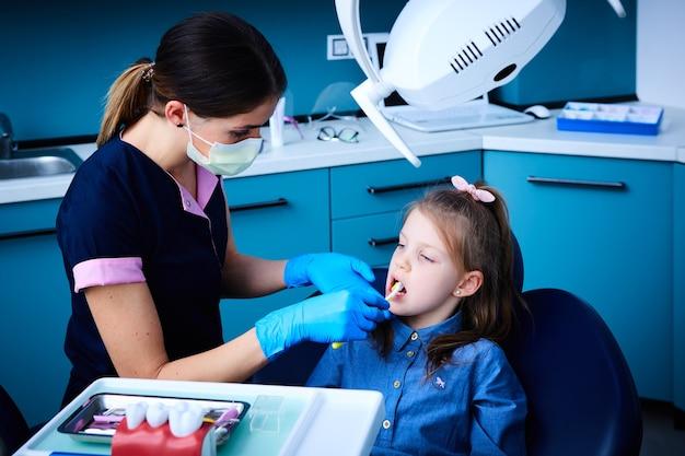 Nettes kleines mädchen, das in der zahnarztpraxis sitzt