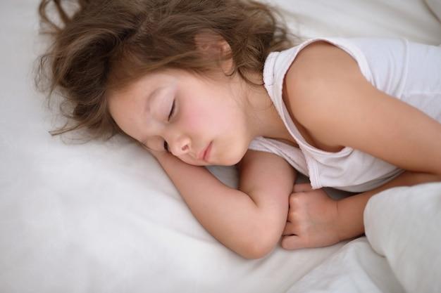 Nettes kleines mädchen, das in einem bett schläft