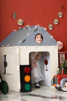 Nettes kleines mädchen, das in einem papphaus sich versteckt und mit einem großen spielzeuglöschfahrzeug spielt. glückliche kindheit.