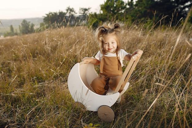 Nettes kleines mädchen, das in einem park mit weißem wagen spielt