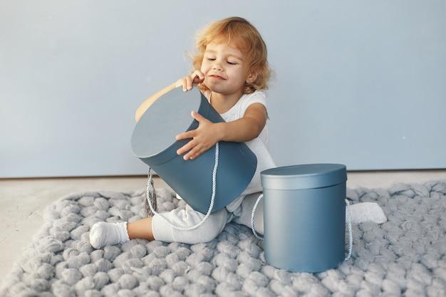 Nettes kleines mädchen, das in einem studio mit geschenkbox sitzt