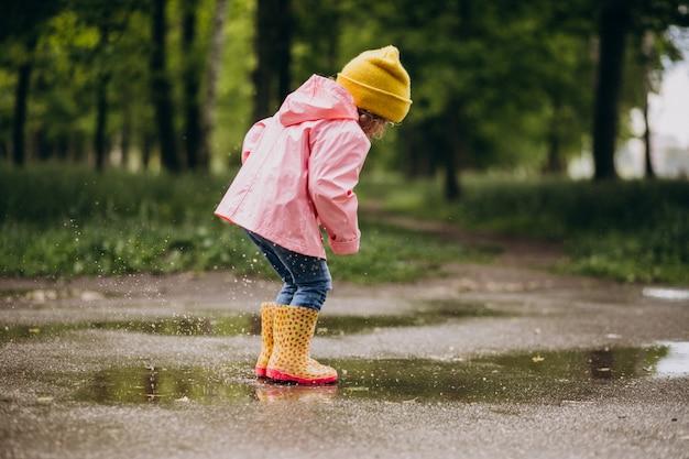 Nettes kleines mädchen, das in einer pfütze in einem regnerischen wetter springt