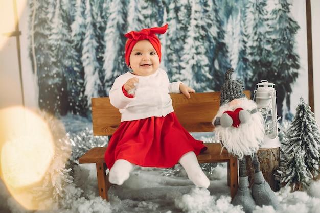 Nettes kleines mädchen, das in weihnachtsdekorationen sitzt