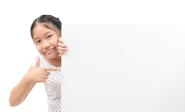 Nettes kleines mädchen, das leere plakatwand lokalisiert auf weißem hintergrund, fahne und werbung für eingabetextkonzept zeigt.