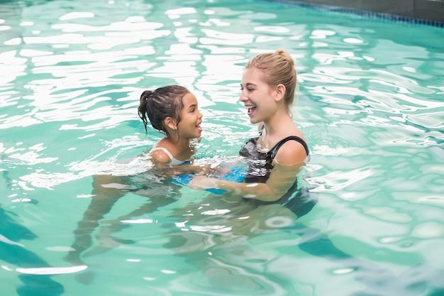 Nettes kleines mädchen, das lernt, mit trainer zu schwimmen