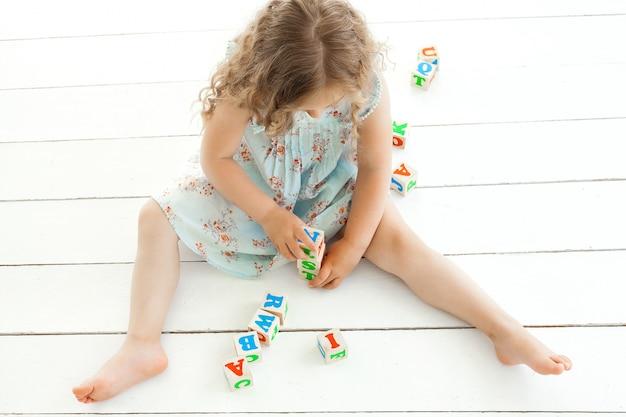 Nettes kleines mädchen, das mit abc-würfeln spielt. kind lernt