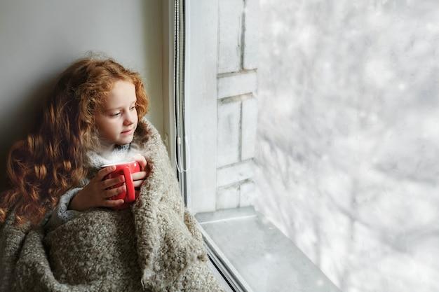 Nettes kleines mädchen, das mit einer schale heißem kakao am fenster sitzt und auf erstem fallendem schnee schaut