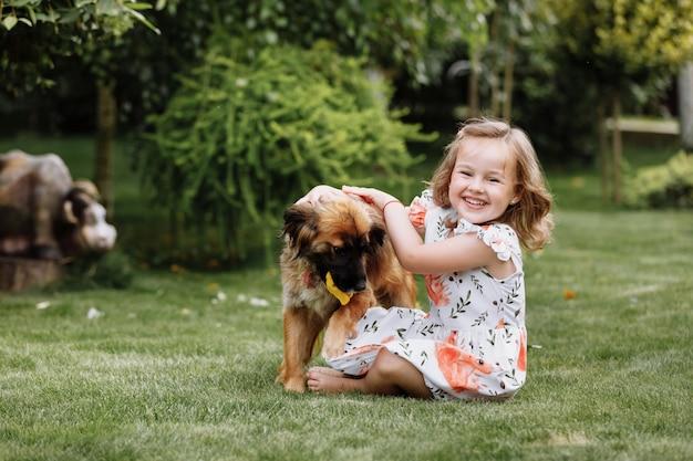 Nettes kleines mädchen, das mit ihrem hund spielt